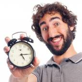 Young bearded man with a clock — Стоковое фото