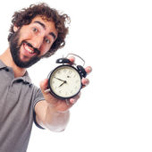 Young bearded man with a clock — Stock Photo