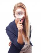 Young cool woman with a magnifier at her eye — Stock Photo
