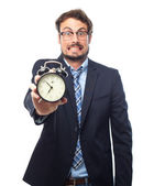 Young crazy businessman with an alarm clock — Stock Photo