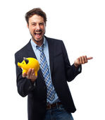 Young crazy businessman with a piggy bank — Stock Photo