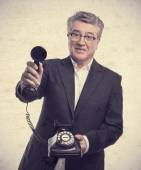 Senior cool man offering a phone — Stock Photo