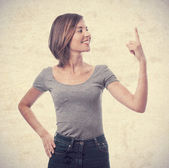 Young cool woman pointing up — Stockfoto