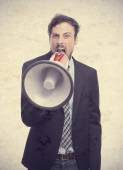Young crazy businessman shouting on megaphone — Stock Photo