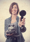 Young cool woman offering a telephone — Stockfoto