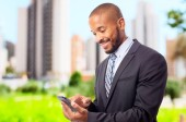 Young cool black man with touch screen phone — Stock Photo