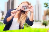 Young cool woman joking with a magnifier — Stok fotoğraf