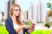 Young cool woman with touch screen phone — Stock Photo