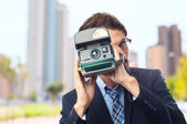 Young crazy businessman taking a photo — Stockfoto