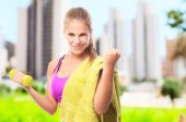 Young cool woman with dumbbell and a towel — Stock Photo