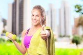 Woman with a dumbbell and a towel — Stock Photo