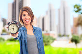 Young cool woman with alarm clock — Foto de Stock