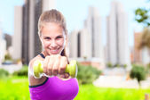 Young cool woman with a dumbbell — Stock Photo