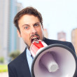 Young crazy businessman shouting on megaphone — Stock Photo #65687077