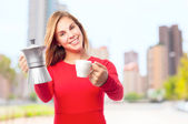 Young cool woman with cup and a kettle — Stock Photo