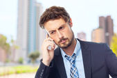 Young crazy businessman speaking on phone — Stock Photo