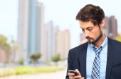 Young crazy businessman wrinting on phone — Stock Photo