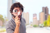 Young crazy man with a magnifier — Stock Photo