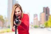 Young cool woman with a gun — Stock Photo