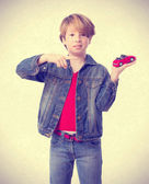Confused boy pointing to a toy car — Stock Photo