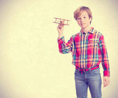 Dreamer kid holding a wood plane — Stock Photo