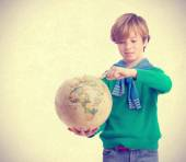 Dreamer child pointing a place in a world globe — Stock Photo