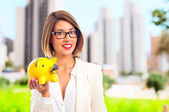 Young cool woman with a piggy bank — Stock Photo