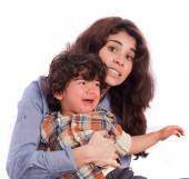 Concerned girl holding her weepy son — Stock Photo