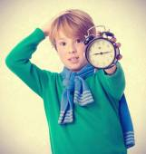 Worried child holding an alarm clock — Stock Photo