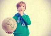 Pensive boy holding a world globe — Stock Photo