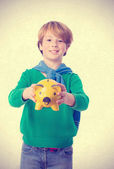 Happy child saving with a piggy bank — Stockfoto