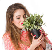 Young girl smelling a plant — Stock Photo