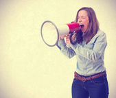 Young woman shouting by megaphone — Stock Photo
