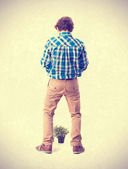 Teenager with plant and urinate gesture — Stock Photo