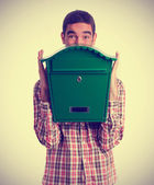 Surprised boy holding a postbox — Stock Photo