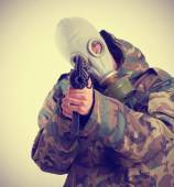Militar with a rifle and a gas mask — Stock Photo