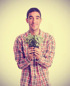 Young man offering a plant — Stock Photo