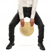 Businessman lifting an euro coin — Stockfoto