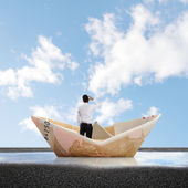 Man into a bill boat on a puddle — Stock Photo