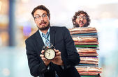 Young crazy businessman with an alarm clock — Stock Photo