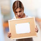 Blond woman with cork board — Stock Photo