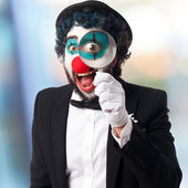 Clown with a magnifier glass — Stock Photo
