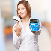 Blond woman with calculator and credit card — Stock Photo