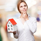 Blond woman with a small house thinking — Stock Photo