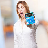 Blond surprised woman with calculator — Stock Photo