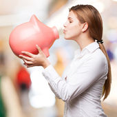 Blond woman with a piggy bank — Stock Photo