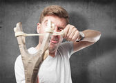 Blond man with a slingshot — Stock Photo