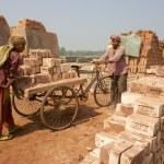 Постер, плакат: Two workers move bricks at a factory in Dhaka Bangladesh
