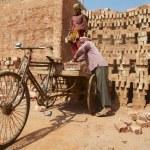 Постер, плакат: Two workers load bicycle with bricks in Dhaka Bangladesh