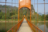 Pedestrian bridge across Nam Song river in tourist oriented town of Vang Vieng, Laos. — Stock Photo